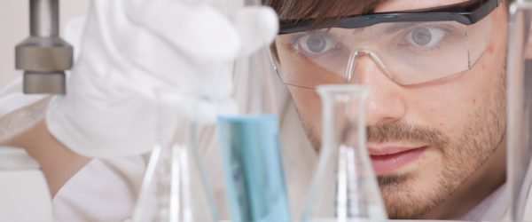 Male,Scientist,In,Research,Lab,Holding,Glass,Flask,With,Blue